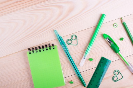 School creative desk with green stationery. Colorful stationery, place for text. Place for caption, top view Stock Photo