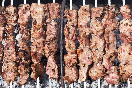 Unfinished kebabs close-up. Photo of cooking shish kebab near. The main picnic dish