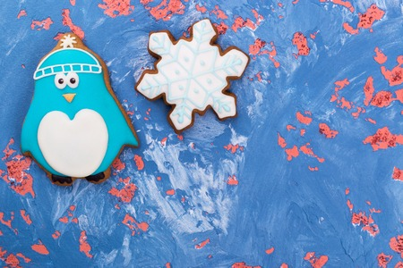 Place for congratulations near sweet gift. Gingerbread penguin, snowflake, place for text