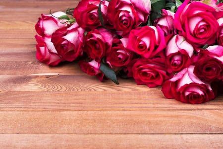 Roses on wooden background. Place for text, bouquet of red roses
