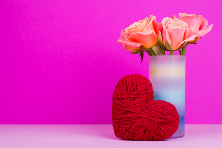 Red heart of thread, orange roses, free place. Beautiful flowers in vase, heart on pink background. St. Valentine's Day