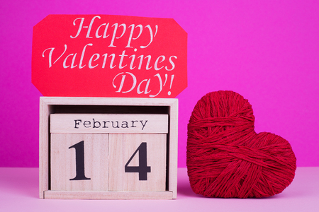 February 14 on calendar, heart, greeting card. Wooden calendar and heart for Valentine's Day