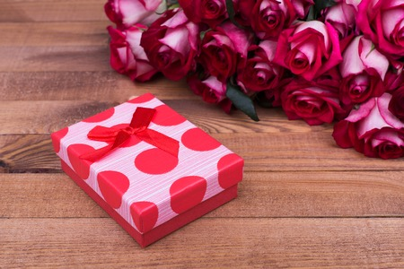 Red box with bow, roses. Beautiful roses and gift box 版權商用圖片