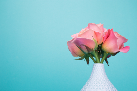 Bright roses in light blue vase. Vase, orange flowers on turquois background. Place for text