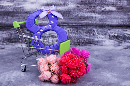 Purple number in shopping trolley. Trolley, eight, flowers on gray background. Artificial flowers on March 8