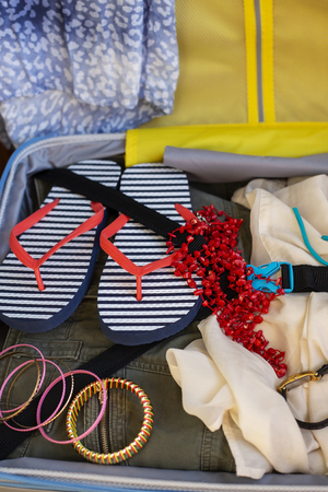 Open suitcase fully packed with folded women's clothing and accessories. Female luggage with things Stock Photo