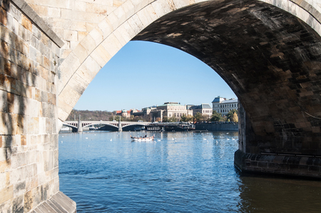 View from under the Charles Bridge. Boat with fishermen near bridge in Prague 版權商用圖片