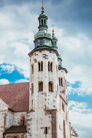 Towers of old church in Krakow, Poland. Fluffy clouds over ancient building Stok Fotoğraf