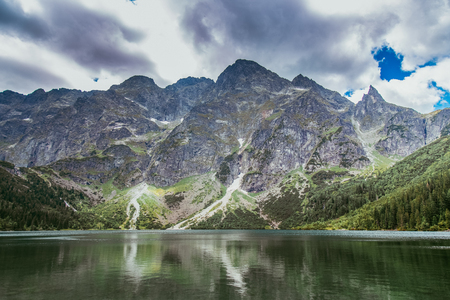 Clouds over high mountains and lake. Mountains of Tatra and lake Morskie Oko. Place where want to return