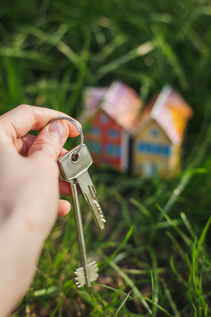 Keys in hand against background of house. Selling real estate concept with house and key