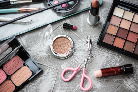 Eye shadow and other cosmetics on background. Daily cosmetics on table