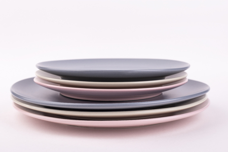 Set of different plates of gray, pink and olive colors, isolate. Plates, saucers, bowls and deep plates on white background