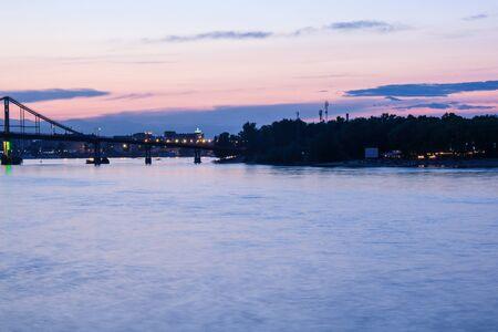 Beautiful sunset at the bridge. High bridge, river, ships and bright sunset. Kiev, Ukraine Stock Photo