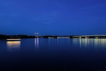 Evening view of river and bridge with lights. Moored ships on shore, bridge, night surface. Kiev, Ukraine