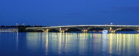 Ships on shore, bridge, night surface. Evening view of river and bridge with lights. Kiev, Ukraine Stock Photo