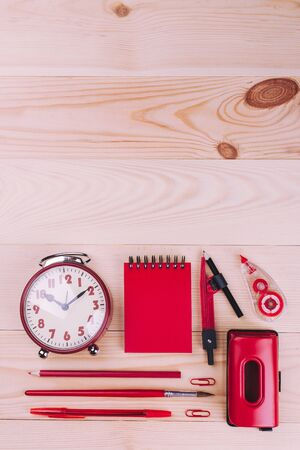 Notebook and other stationery in red color. School desk with colorful stationery. Red back to school concept.