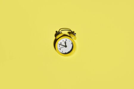 Bright alarm clock on yellow background. Free space at color alarm clock
