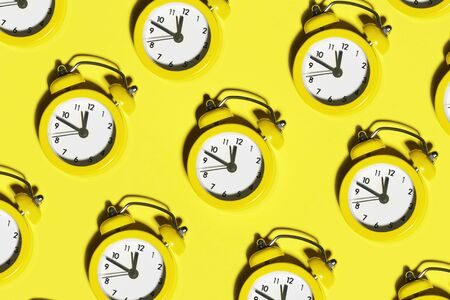 Color alarm clocks on yellow background. Many bright alarm clocks with shadows