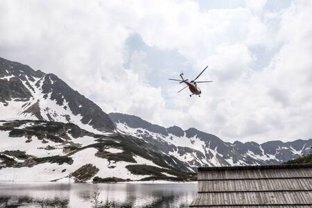 Helicopter over mountain lake. Wooden hut in mountains and red helicopter