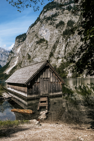 Old river house in mountains. Wooden dock houses on lake with typical wooden pier. Bavarian Alps, Germany
