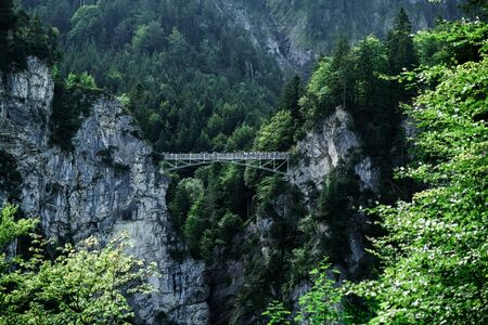 The ancient iron bridge of Mary over the deep abyss between the rocks opposite Neuschwanstein Castle