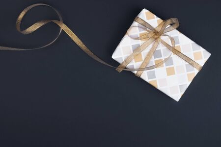 Gift box with ornament and gold ribbon on a black background. Stock Photo