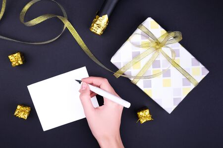 Gift box with ornament and gold ribbon on a black background, woman hand and white card for text Stock Photo