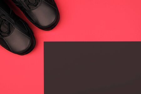 Two pure black sneakers on a redn background with black place for text