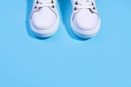Pure white sneakers on a light blue background with a place for text