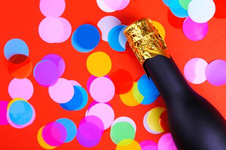 A bottle of champagne and confetti on a red-green background with a place for your congratulatory inscription
