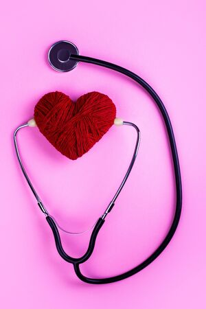 Red heart and a stethoscope listening to him on a pink background