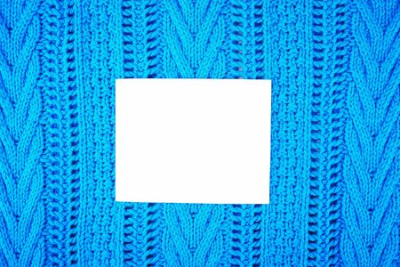 White blank sheet for inscription on the background texture of a warm blue sweater with patterns Stock Photo