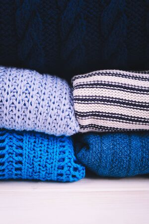 A stack of varied blue sweaters lie on a white wooden background