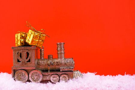 Big steam train and gift box lie in the snow on a bright red background, New Year mood Stock Photo