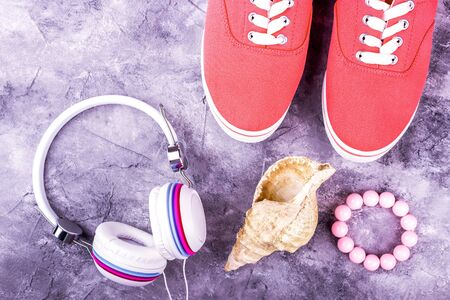 Bright coral sneakers and multi-color headphones, a pink bracelet and a seashell Фото со стока