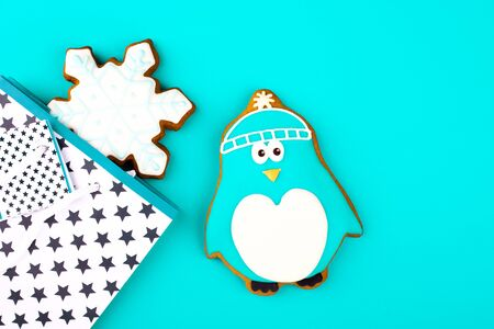 Gingerbread cookies in the shape of a penguin and snowflakes in a gift bag with on a bright turquoise background Stock Photo