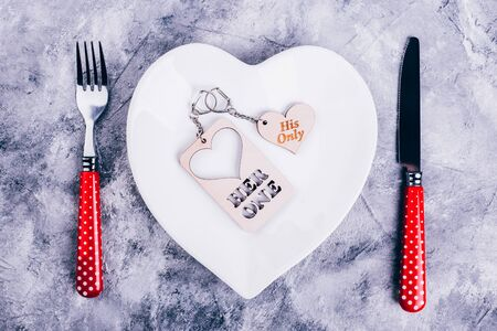 White heart-shaped plate and red polka dot cutlery on a concrete table, keychain for lovers