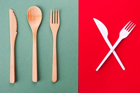 Bamboo spoon, fork and knife on a green background and plastic cutlery on a red background, eco concept Stock Photo