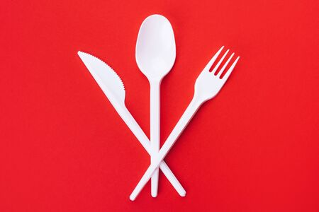 White plastic spoon, fork and knife on a red background lie across, eco concept