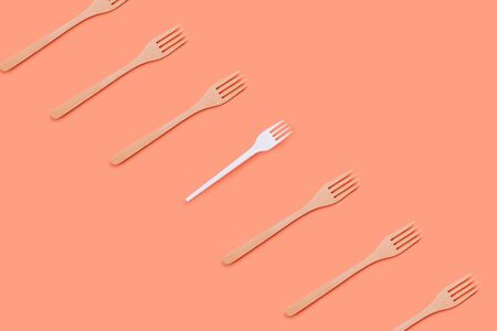 Many bamboo and one plastic fork on a peach background, eco concept