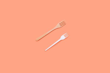 Bamboo and plastic fork on a peach background, eco concept