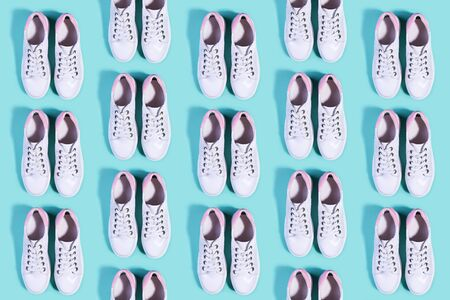 Pure white sneakers on a bright turquoise background pattern