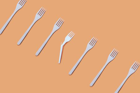 Many bamboo and one broken plastic fork on a beige background, eco concept Stock Photo