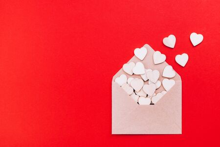 Wooden hearts in an open craft envelope with place for text, holiday of love on red background