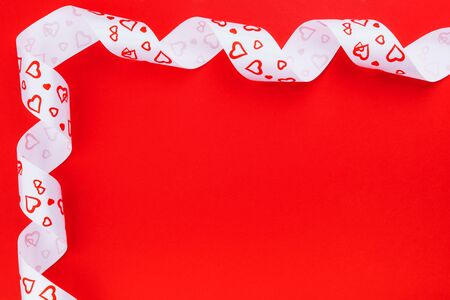 White ribbon with hearts on bright red background with place for text on Valentines Day or Xmas Imagens
