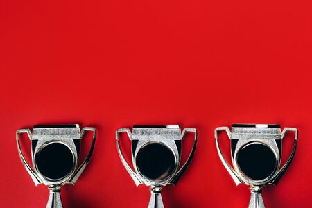 Three winner cups as trophies on bright red background with place for text