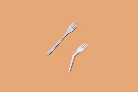 Bamboo and broken plastic fork on a beige background, eco concept