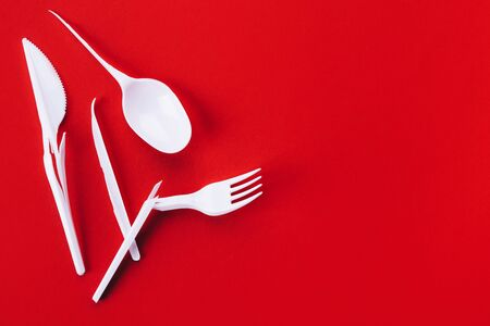 White broken plastic spoon, fork and knife on a red background with place for text, eco concept Stock Photo