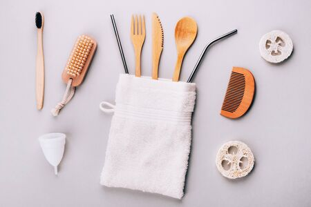 Bamboo cutlery, loofah sponges, wooden comb, toothbrush, paper bag, menstrual cup and cotton branch on a bright gray background Stok Fotoğraf