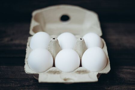 Six white eggs in an open package close-up on a dark wooden background, preparation for Easter